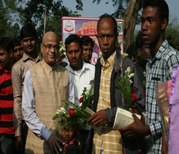 Shri Sandip Mitra, Assistant Hgh Commissioner receiving a new citizen with flowers at Changrabandha